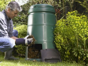 Gardener tending garden and removing soil from compost bin